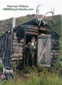 Bearded man in doorway of old cabin