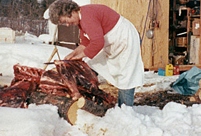 woman butchering a caribou outdoors on a log